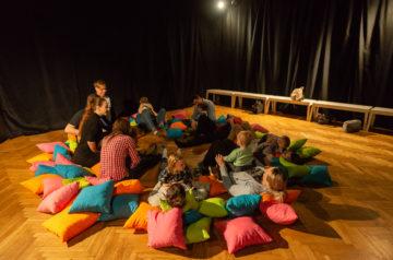 Grupa dzieci i dorosłych siedzi na podłodze na kolorowych poduszkach podczas warsztatów teatralnych w Teatrze Miejskim w Gliwicach