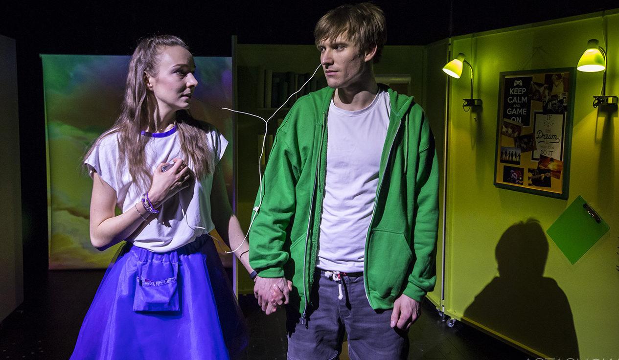 Dwójka młodych ludzi trzyma się za ręce, patrzą na siebie. Dziewczyna trzyma w ręku telefon z podłączonymi słuchawkami. Jedna słuchawka jest w uchu dziewczyny, drugiej słucha chłopak.
