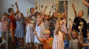 Dzieci trzymają w rękach samodzielnie przygotowane lalki teatralne zrobione z drewnianych łyżek