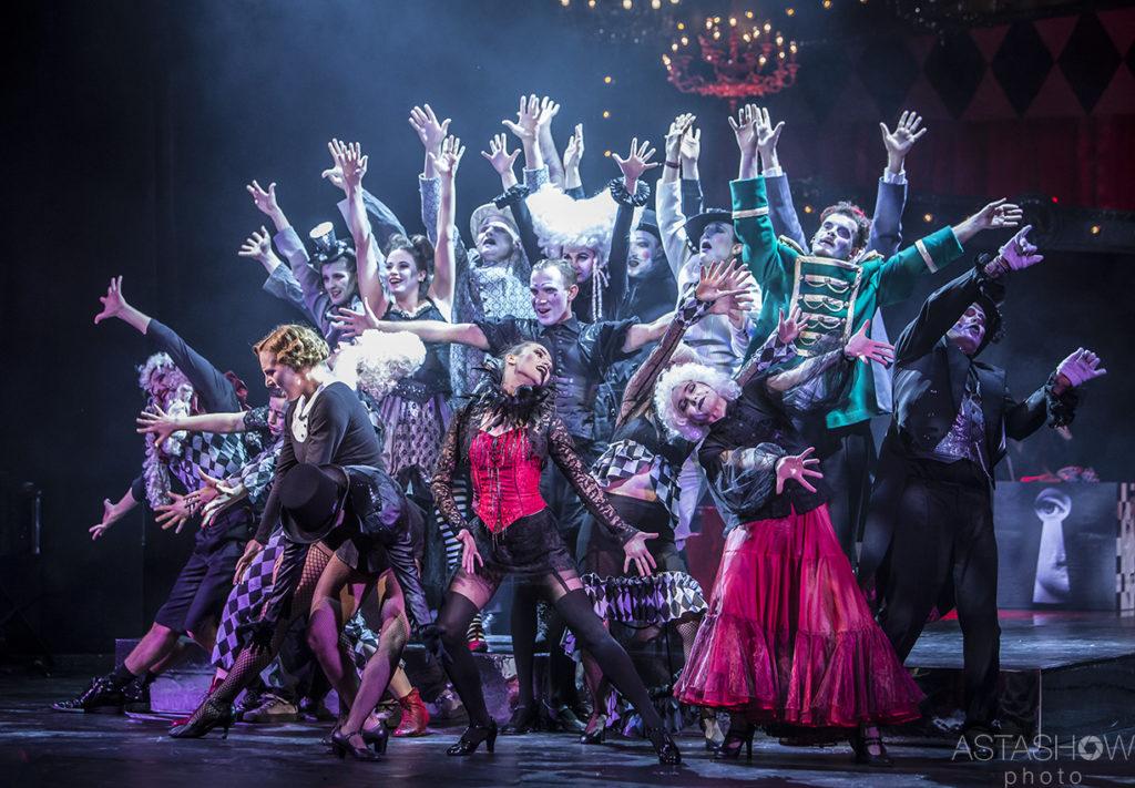 """Grupa kilkunastu aktorów w tańcu na scenie w spektaklu """"Tuwim dla dorosłych"""". Aktorzy mają na sobie ekspresyjne makijaże i kabaretowe kostiumy."""