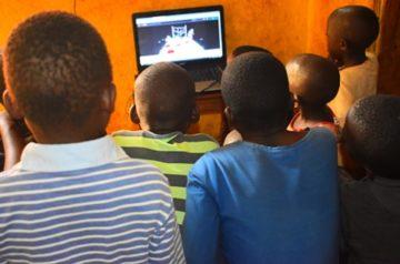 Dzieci w Ugandzie oglądają spektakl Pod kolor na ekranie komputera