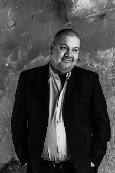 Na zdjęciu Marek Dyjak na tle betonowej ściany.