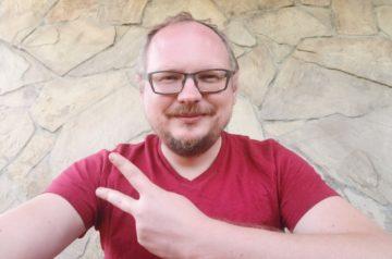 Andriei_Kurieichik, autor sztuki Białoruś obrażona, robi sobie selfie. Ma na sobie czerwoną koszulkę i jest uśmiechnięty. Jedną ręką pokazuje V – znak wolności. Zdjęcie z archiwum autora.