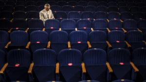 Na zdjęciu, na pustej widowni Teatru Miejskiego w Gliwicach siedzi samotny aktor, Błażej Wójcik. Ubrany jest w elegancki jasny garnitur. Zdjęcie Jeremi Astaszow