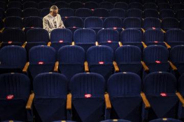 Grudniowa uczta teatralna. Na zdjęciu, na pustej widowni Teatru Miejskiego w Gliwicach siedzi samotny aktor, Błażej Wójcik. Ubrany jest w elegancki jasny garnitur. Zdjęcie Jeremi Astaszow