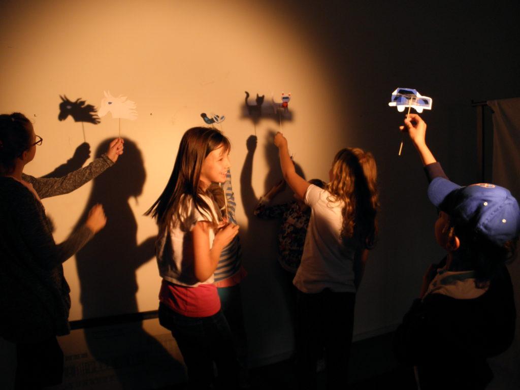 Na zdjęciu warsztaty teatru cieni dla dzieci. Uczestnicy trzymają w rękach stworzone lalki cieniowe z wykałaczek i papierowych wycinanek. Lalki rzucają cień na ścianę.