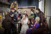 """Scena ze spektaklu """"Ożenek"""". W centrum Karolina Burek w sukni ślubnej, wokół aktorzy w charakteryzacji i kostiumach do spektaklu."""
