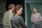 """Aktorzy na scenie w spektaklu """"Powrót"""" . Trójka dorosłego rodzeństwa rozmawia."""