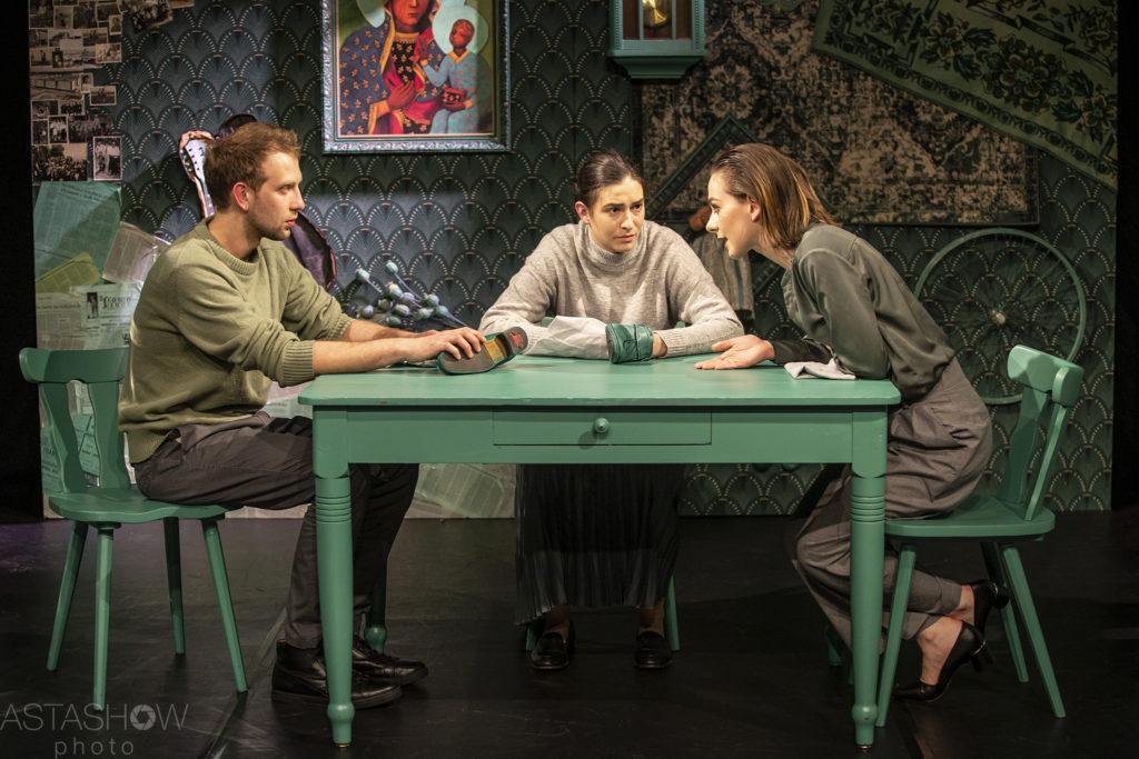 Trójka dorosłego rodzeństwa prowadzi rozmowę przy stole.