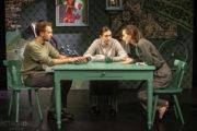 """Aktorzy na scenie w scenografii spektaklu """"Powrót"""". Przy stole siedzi trójka dorosłego rodzeństwa i rozmawia."""