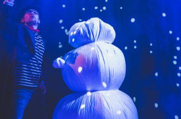 """Zdjęcie ze spektaklu """"Malutka Czarownica"""".Na zdjęciu na tle światełekaktor żongluje drewnianą miotłą nad głową białego dmuchanego bałwana."""