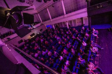 Do Teatru w styczniu? Widok z balkonu na widownię Teatru Miejskiego w Gliwicach. Na widowni w odstępach siedzą widzowie. Na twarzach mają maseczki. W lewym górnym rogu, na pierwszym planie, widać reflektor. Autorem zdjęcia jest Jeremi Astaszow