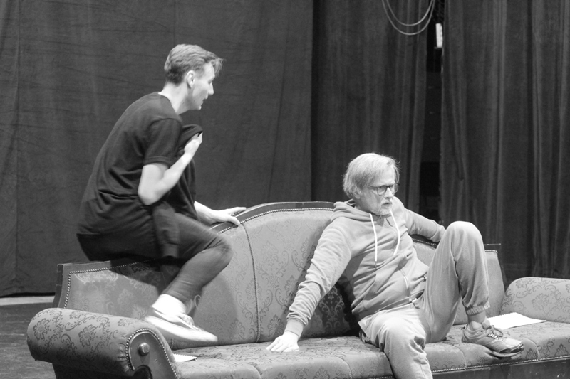 Zdjęcie z próby do spektaklu Ożenek. Dwóch aktorów rozmawia siedząc na kanapie.