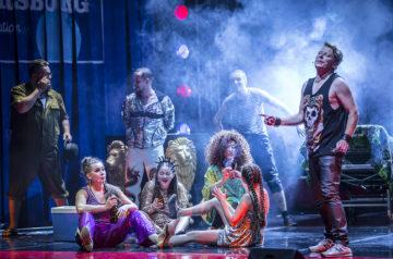 Na podłodze siedzi grupa kobiet w kolorowych, połyskujących klubowych strojach. Za kobietami w oparach dymu śpiewający mężczyźni.