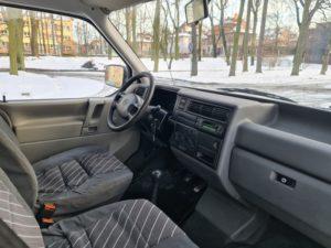 Wnętrze samochodu. Widać fotele i deskę rozdzielczą. Za oknem jasno i leży śnieg.