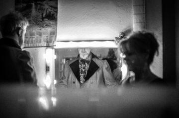 """W garderobie aktor Krzysztof Prałat mierzy kostium do spektaklu """"Ożenek"""". Sylwetka aktora odbija się w podświetlanym lustrze. Przymiarce przygląda się krawcowa."""