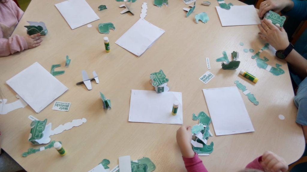 Na drewnianym stole rozłożone arkusze papieru, kleje, nożyczki. Ręce dzieci sięgają po materiały plastyczne.