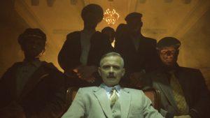 Na fotelu w białym garniturze siedzi aktor Błażej Wójcik w charakteryzacji przypominającej Aleksandra Łukaszenkę. Za nim w półcieniu kilku mężczyzn.