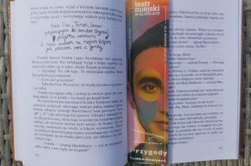 """Otwarta książka """"Przygody Tomka Sawyera"""". W środku książki zakładka Teatru Miejskiego w Gliwicach promująca spektakl """"Przygody Tomka Sawyera"""""""