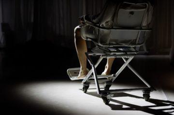 Zdjęcie ze spektaklu Stan Zero z Akademii Teatralnej w Bytomiu. Na zdjęciu fragment wózka iwalidzkiego i siedząca na nim osoba. Widać tylko dolną część oświetloną białym światłem. Autorem zdjęcia jest Julia Banduch.