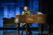 """Mateusz Trzmiel w roli Mozarta w spektaklu """"Amadeusz"""". Aktor gra na fortepianie."""
