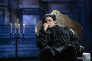 Błażej Wójcik w roli Salieriego. Aktor w czarnym kostiumie siedzi na fotelu zamyślony.