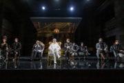 """Scena zbiorowa ze spektaklu """"Amadeusz"""". Pośród grupy aktorów w ciemnych strojach wyróżnia się Krzysztof Prałat w białym stroju i peruce."""