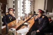 """Aktor Maciej Piasny spogląda do lustra w garderobie teatralnej. Mężczyzna ma na sobie kostium do spektaklu """"Ożenek"""""""