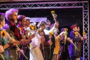 """Aktorzy stoją na scenie podczas oklasków po premierze spektaklu """"Ożenek"""". W rękach trzymają otrzymane kwiaty słonecznika."""