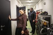 """Aktorzy Aleksandra Maj i Łukasz Kucharzewski w kostiumach do spektaklu """"Ożenek"""" stoją obok garderoby."""
