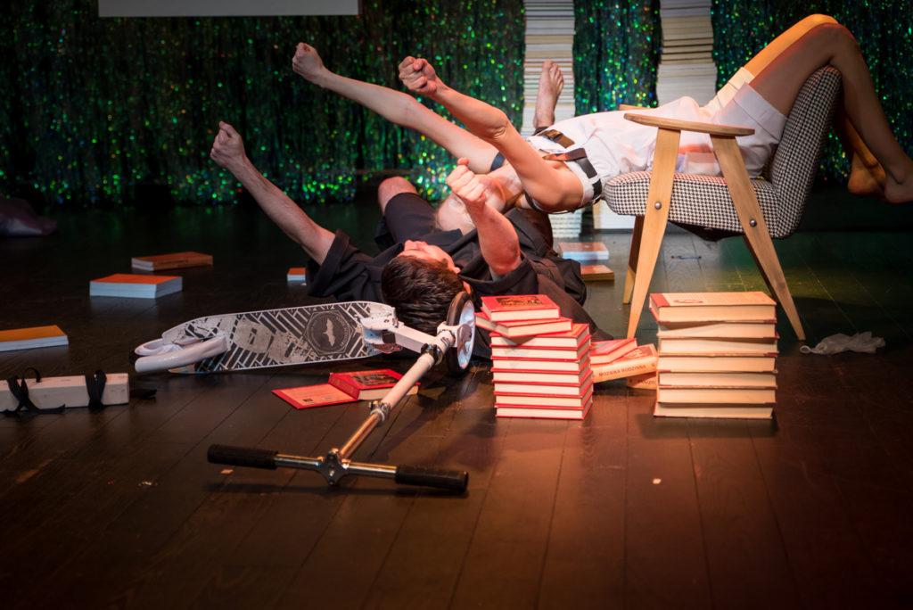 """Scena ze spektaklu """"Mała Syrena"""". Wiktoria Czubaszek i Kornel Sadowski leżą, podnosząc ręce do góry. Wokół stosy książek i przewrócona hulajnoga."""
