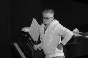 """Błażej Wójcik na scenie w próbie do spektaklu """"Amadeusz"""" stoi oparty o fortepian."""