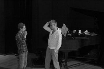 """Błażej Wójcik i Mateusz Trzmiel na scenie w próbie do spektaklu """"Amadeusz"""", w tle fortepian"""