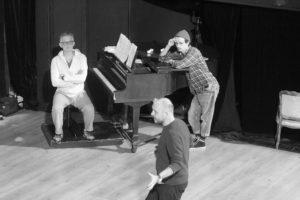 Błażej Wójcik siedzi przy fortepianie, o który opiera się Mateusz Trzmiel. Z przodu reżyser Norbert Rakowski.