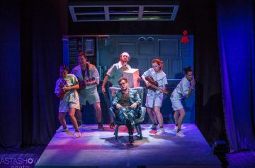 Na środku sceny siedzi mężczyzna w okularach. Wokół niego tańczące i śpiewające osoby trzymają w rękach niewielkie instrumenty muzyczne.