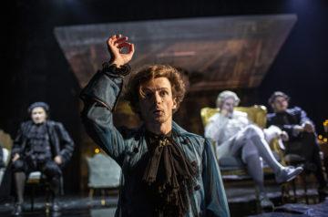 Mateusz Trzmiel w roli Mozarta. Mężczyzna podnosi rękę do góry, dyrygując. Za nim na pozłacanym fotelu cesarz Józef II - w tej roli Krzysztof Prałat.
