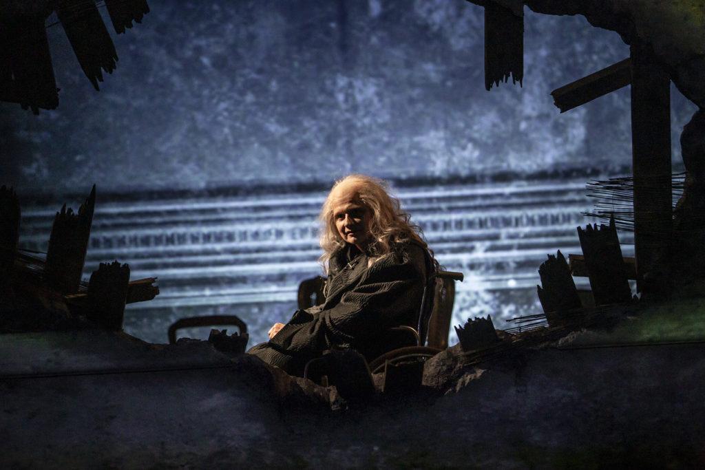 Przez ogromną dziurę w ścianie widzimy starca siedzącego na wózku inwalidzkim - to Antonio Salieri.