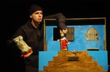 Aktor animuje lalki w teatrzyku stolikowym
