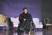 """Aktor Błażej Wójcik podczas próby do spektaklu """"Amadeusz"""". Aktor siedzi na wózku inwalidzkim w kostiumie."""