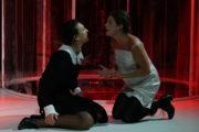 Dwie kobiety klęczące na podłodze kłócą się, jedna krzyczy.