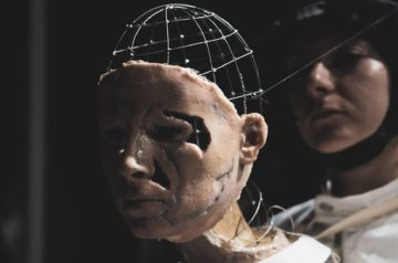 Aktorka trzyma lalkę teatralną. Twarz lalki stanowi odlew twarzy, naznaczony bruzdami. Głowa lalki zbudowana jest z metalowych prętów, połączonych z kaskiem na głowie aktorki.
