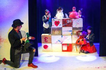 Aktor w ciemnym stroju trzyma lalkę kruka. Obok ściana zbudowana z kolorowych pudeł, za nią aktorzy w kostiumach. Po prawej stronie aktorka trzyma lalkę Malutkiej Czarownicy.
