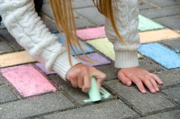 Dziewczynka maluje kredą na płytkach chodnikowych. Zdjęcie: Pixabay