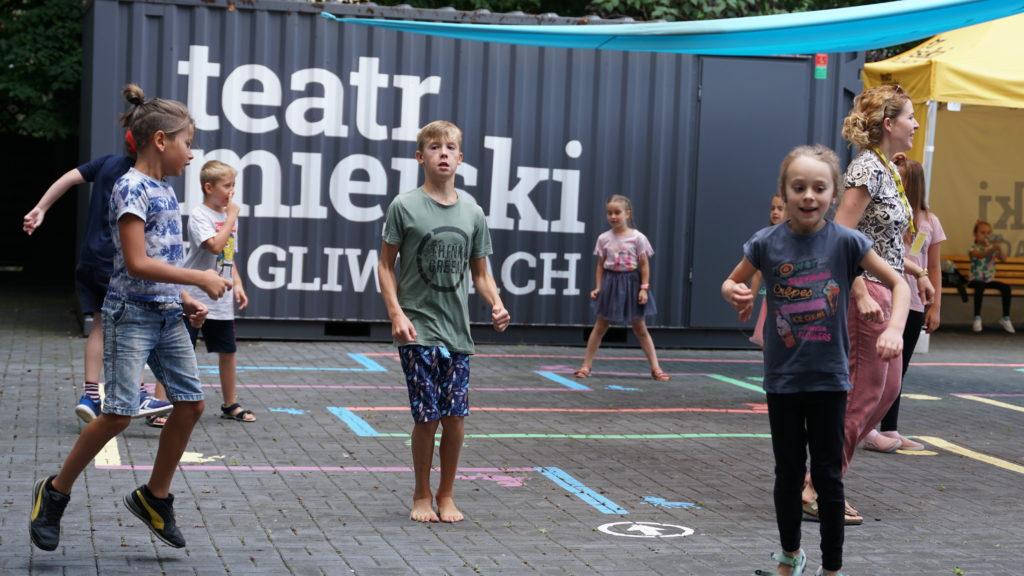 Zabawa na Teatralnym Placu Zabaw. Dzieci i dorośli skaczą po wymalowanych na płytkach chodnikowych zabawach.