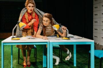 """Scena ze spektaklu """"Plotka"""". Przy stole siedzą dwie aktorki, przykryte kocem. Na stole dwie lampki biurkowe."""
