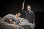 Mężczyzna leżący na łóżku podnosi rękę w geście powitania młodego mężczyzny, który zdejmuje kapelusz na powitanie.