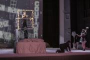 Na drewnianym podium oświetlonym lampkami kobieta śpiewa do mikrofonu. Poniżej mężczyzna klęczący i kobieta w stroju kelnerki.