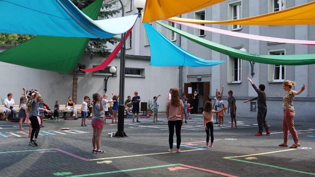 Dzieci stoją w kole na dziedzińcu Teatru Miejskiego w Gliwicach. Nad ich głowami kolorowe materiały pełniące rolę zadaszenia. Dzieci powtarzają ruchy za aktorem.