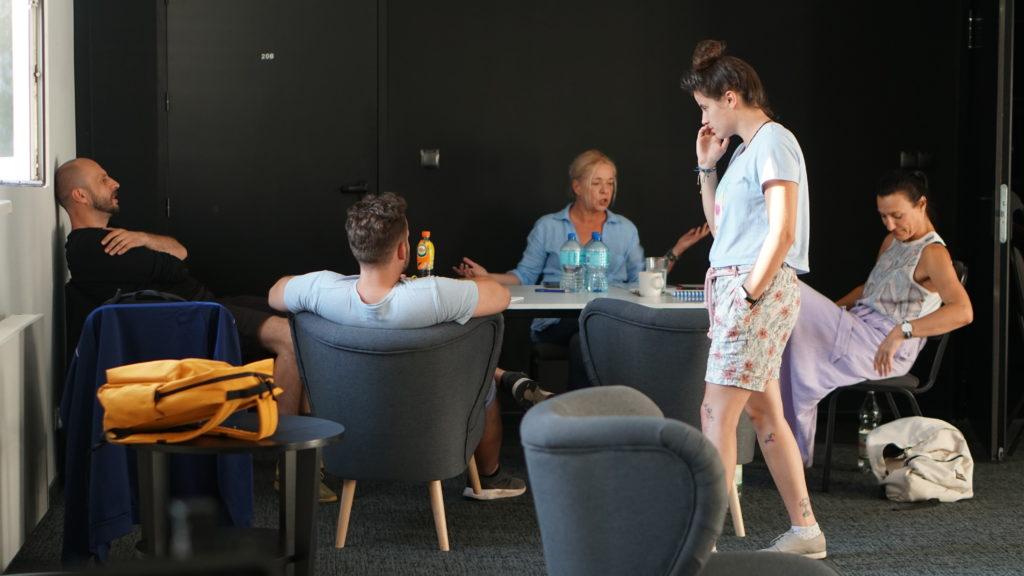 """Pierwsza próba do spektaklu """"Całe życie"""". Przy stole siedzą reżyserka Joanna Oparek i aktorzy."""