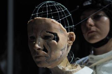 Lalka teatralna ze spektaklu Pokojówki. Twarz lalki wykonana jest z metalowej konstrukcji i tworzywa odwzorowującego rysy ludzkiej twarzy.